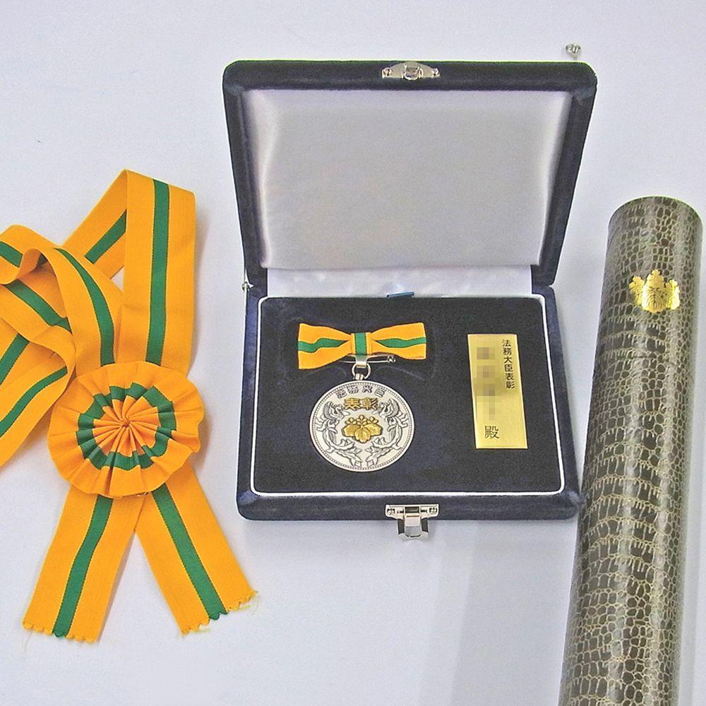 法務大臣表彰とメダル          /                        大きなリボンをしっかり見せて、法務大臣表彰の額装です
